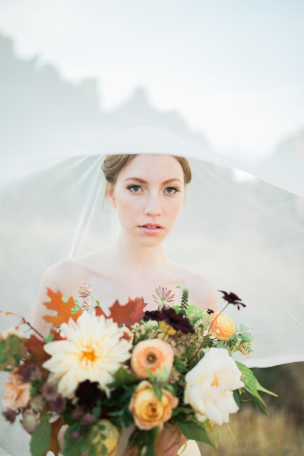 Fall bridal wedding bouquet with peach and burgundy flowers - dahlias, garden roses, chocolate cosmos, and ranunculus by Foraged Floral at Smith Rock, Oregon