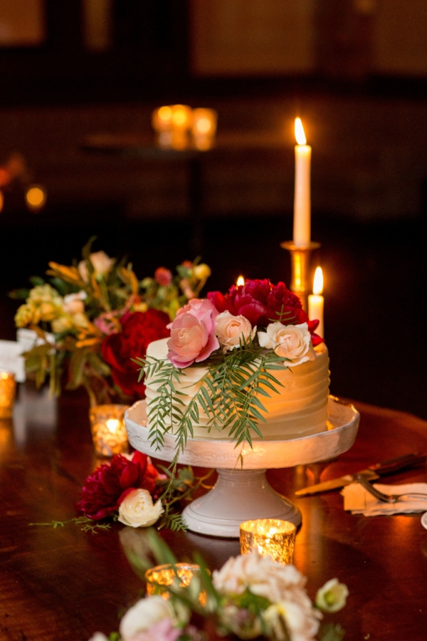 one tier wedding cake accented with pink, peach and burgundy flowers by Foraged Floral