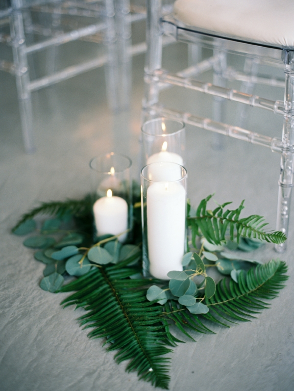 Indoor wedding ceremony aisle decor with candles and greenery by Foraged Floral
