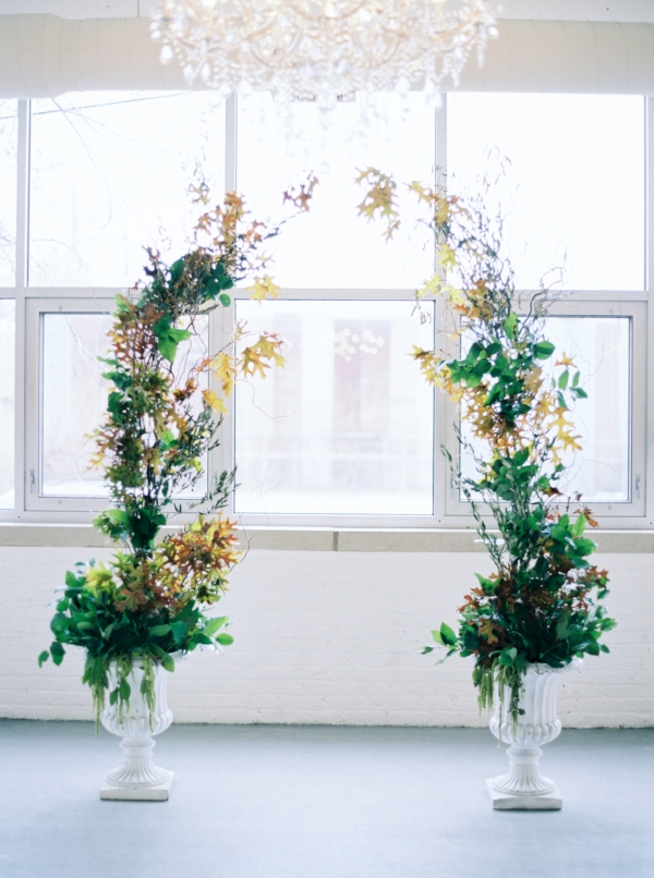 Fall inspired wedding arch with greenery and fall leaves for indoor wedding ceremony at Room 1520 by Foraged Floral in Portland, Oregon