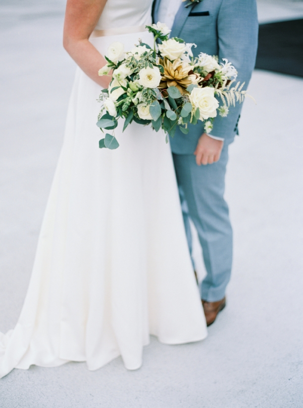 Winter wedding bouquet with white and green flowers like ranunculus, garden roses, berries, succulents and anemones by Foraged Floral from Portland, Oregon.