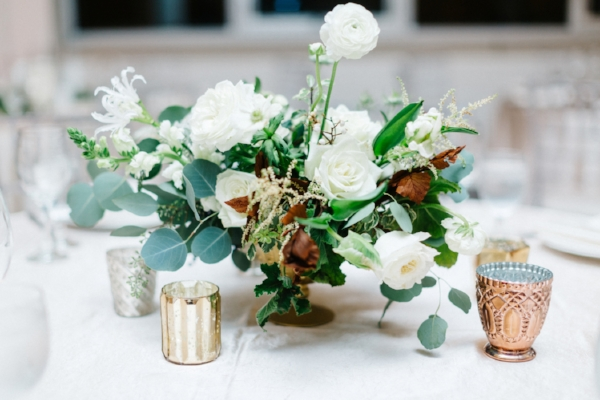 Floral centerpiece for white, green and metallic themed winter wedding made up of ranunculus, garden roses, succulents, berries and more by Foraged Floral based in Portland, Oregon