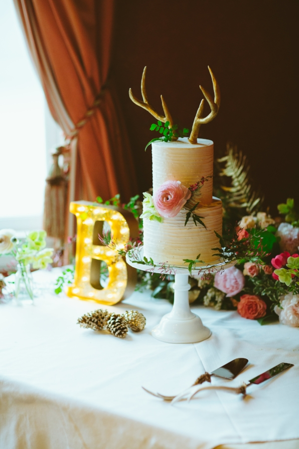 wedding cake with antlers and coral, pink and blush flowers