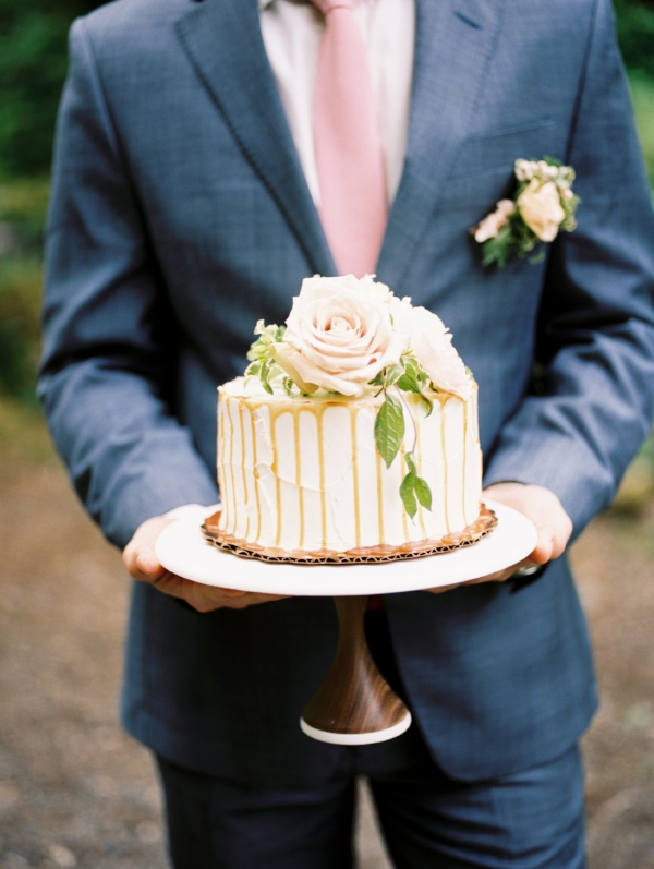 Small, white wedding cake with pink and white flowers on top by Foraged Floral in Oregon