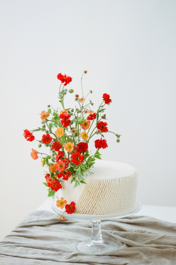 Festive wedding cake inspiration with red and orange fresh flowers by Foraged Floral