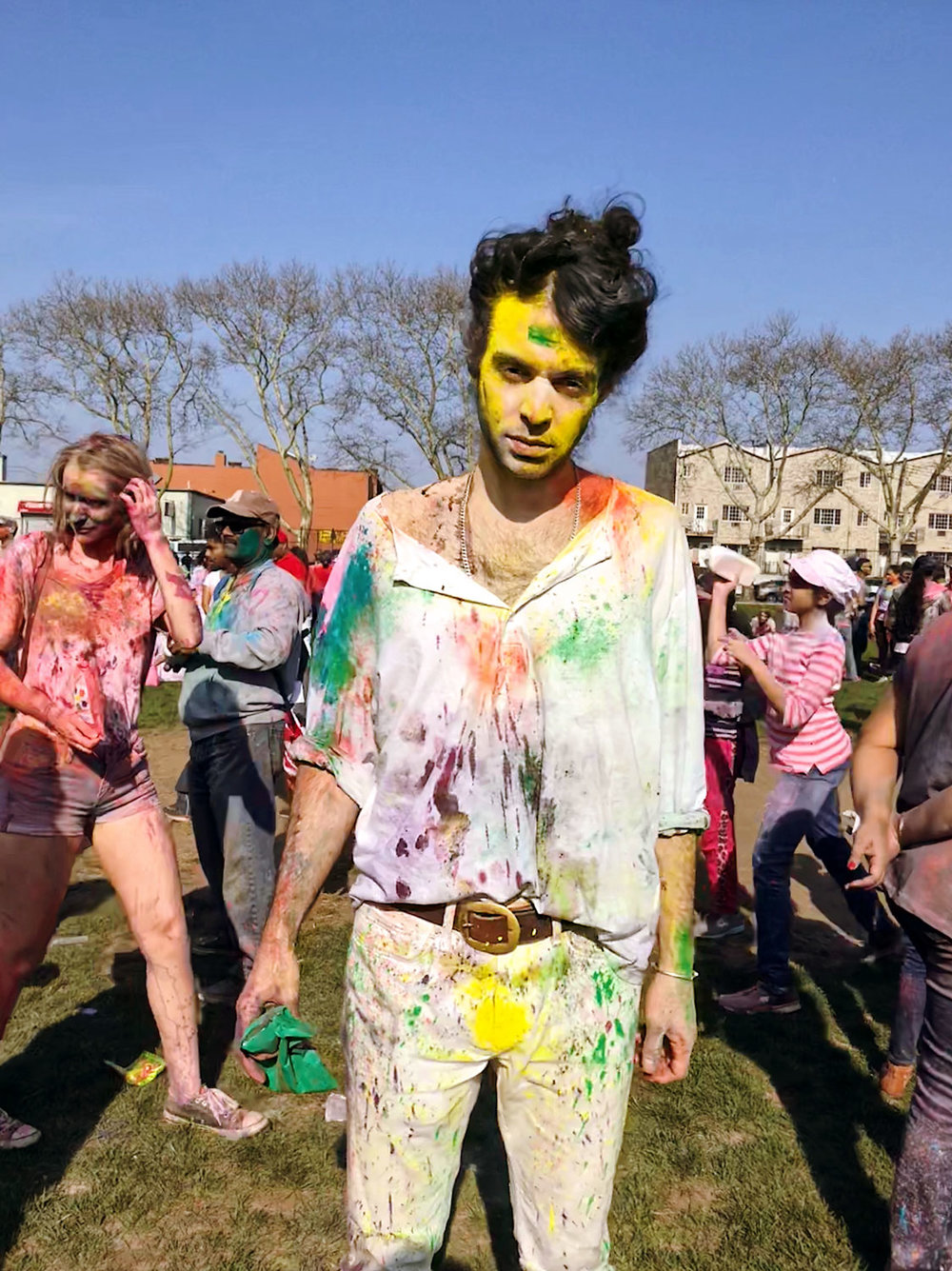 Paul James Read,  adorned in the vibrant colors of Holi, contributes to the celebration with his own Green throwing powder.