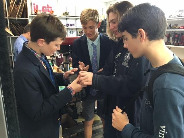 Students collaborating on servo glove design
