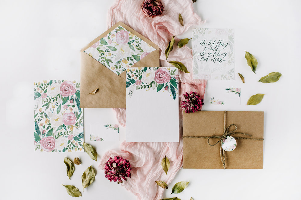 Workspace. Wedding invitation cards, craft envelopes, pink and r