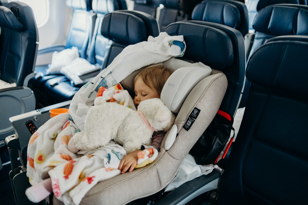 Pre-boarded and ready for flight. Leya sleeps comfortably in her giant car seat that Dad lugs around.