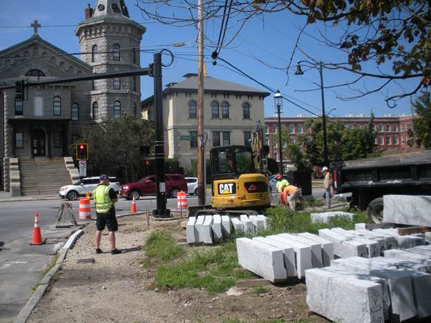Construction crews install new curbs with a new streetlamp in background.