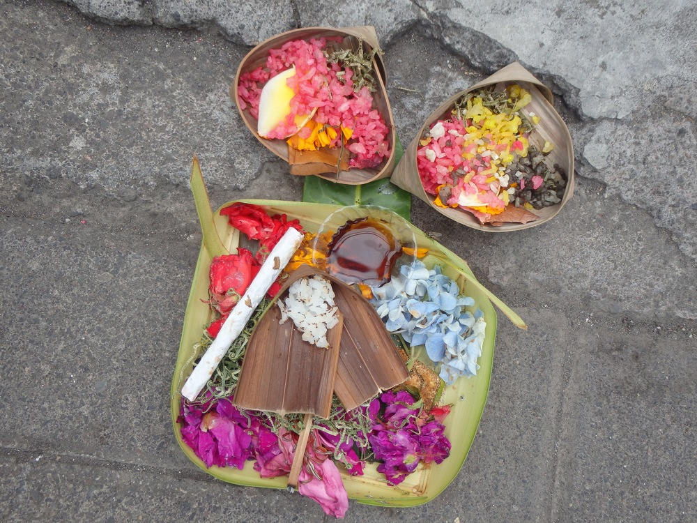 A daily offering to ancestral spirits on the sidewalk in Bali.