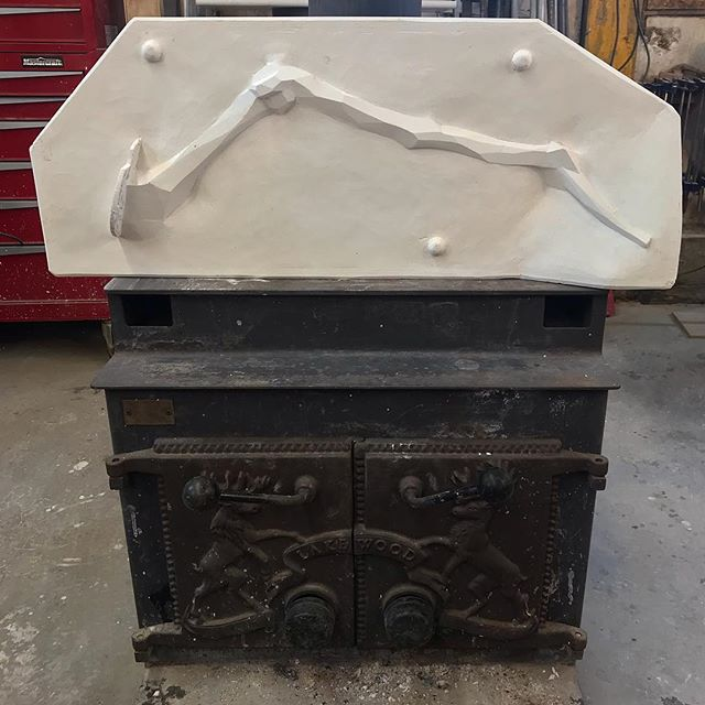 Drying a match plate for a large creature leg on the wood stove.  #designbuild by #jakatelier #creaturetable #bronzecasting #furnituredesign