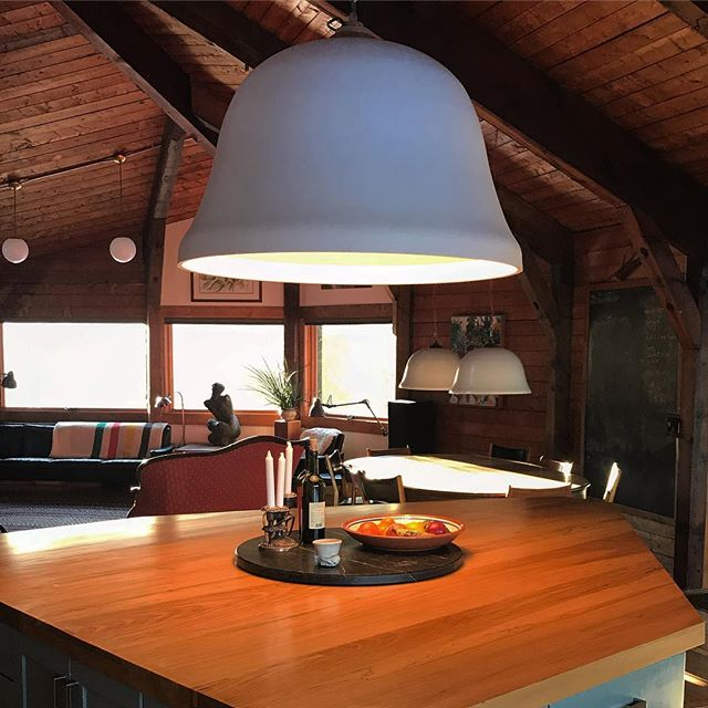 """Spring sunlight streaming in.  41"""" raw plaster bell pendant over the 3"""" thick elm island and the soapstone Lazy Susan. #designbuild by #jakatelier #interiordesign #pendantlights #lightingdesign"""