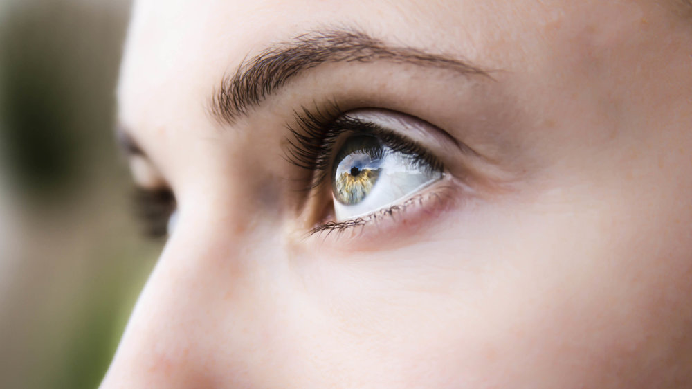 close up of a woman's hazel eyes with sunlight reflecting off of them