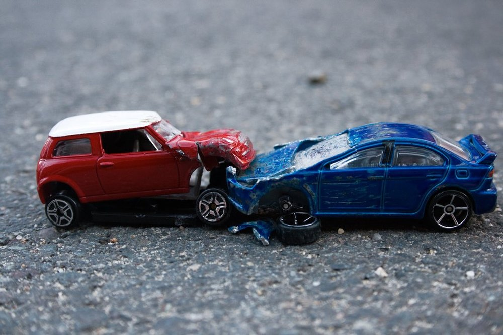 a car accident with model cars of a blue sports car and a red mini cooper