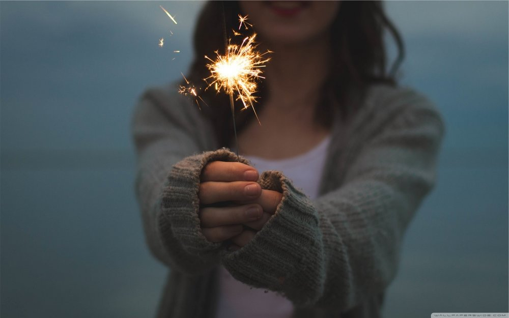 close up of a woman in a sweater holding a sparkler in winter