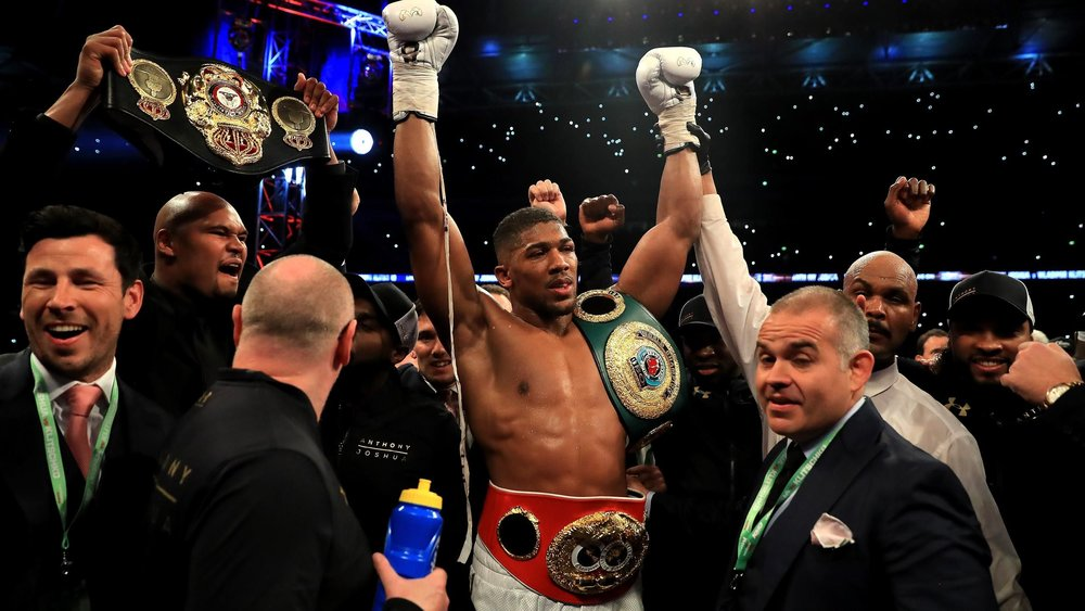 black boxer confidently raising his arms in victory with multiple title belts and people around him