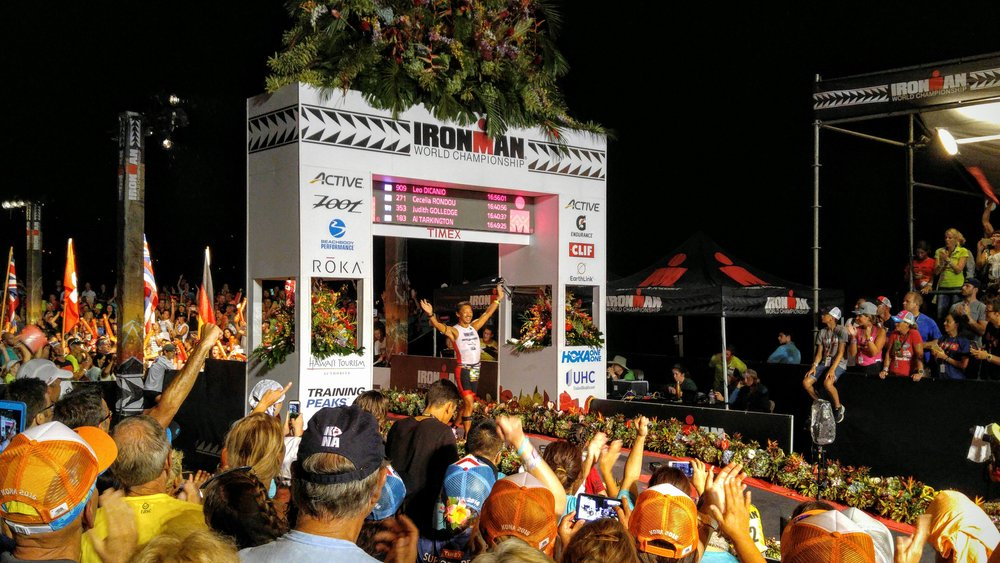 We see a ceremony with crowds of people celebrating the winning of an ironman competition