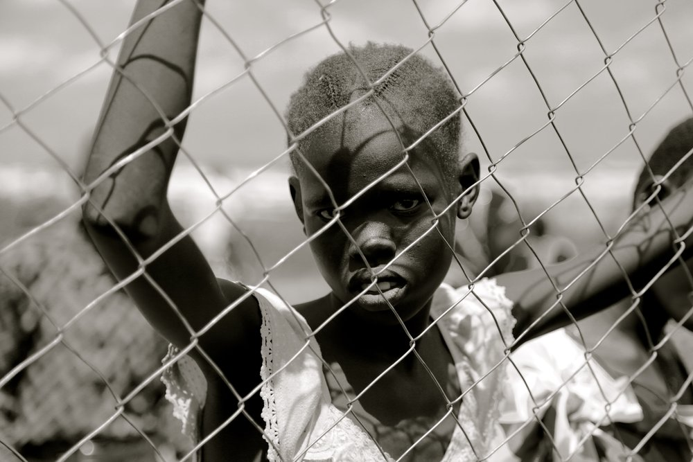 a child from South Sudan suffering as a prisoner behind a chain link fence.