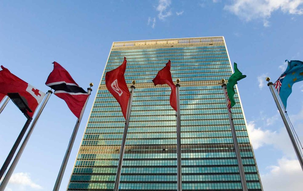 United nations building with flags in front, including Switzerland and others.
