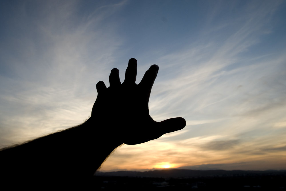 shadowed or dark hand reaching out to God in hope toward a sunrise