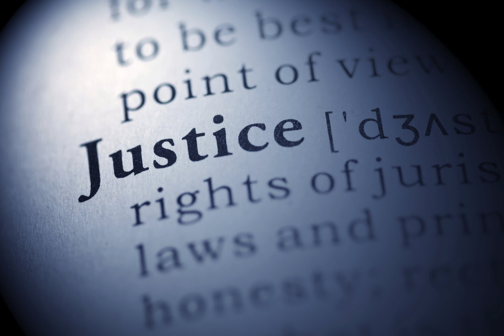 closeup of a definition of justice on the page of a dictionary.