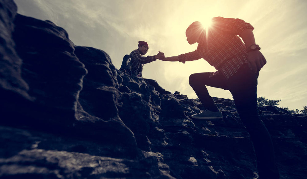 One man helping another man up on a free climb on a mountain top. The sunshine is behind them creating a solar flare behind the man climbing up.