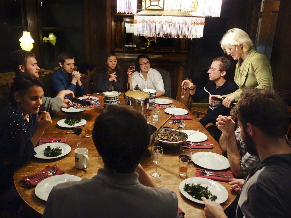 a large communal table with men and women sharing food