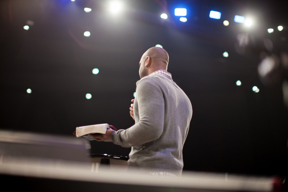 man preaching from behind and without a pulpit; he is simply holding a bible
