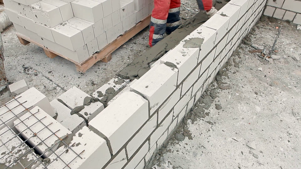 white bricks being built together into a two-story house using mortar and mesh rebar