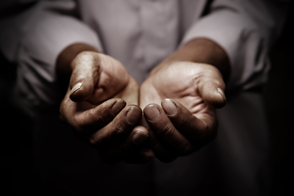 Older african american hands stretched out in humble service or in humility.