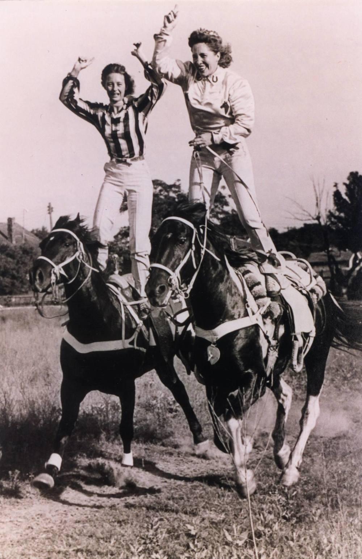 Two girls standing on horses.jpg