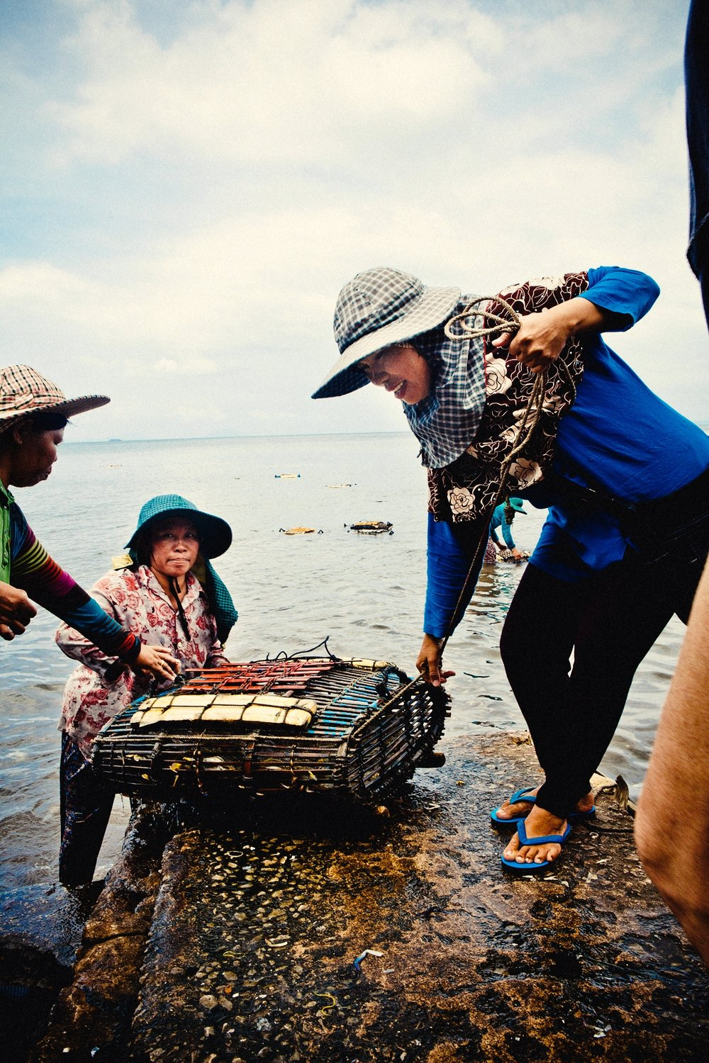 Getting the crab cage from the sea just outside the crab market.