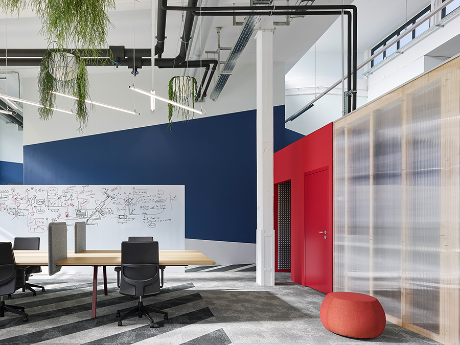 """Bosch's new workspace in southwest Germany is housed in a former production facility. Ubiquitous zinc surfaces, graphic wall and floor treatments, and strewn foliage and furniture add to an eclectic, dreamlike aesthetic. """"We wanted to combine the industrial past of the hall with the actual use of it,"""" says architect Alexander Fehre.   Courtesy Zooey Braun"""
