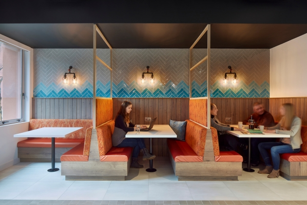 Plywood diner booths are upholstered in orange Kvadrat fabric. Photograph: Mark Cocksedge