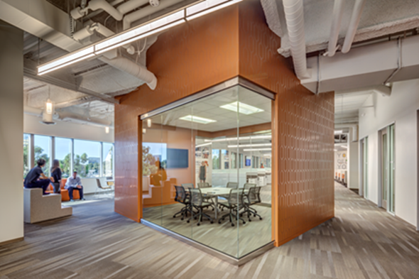 As a part of the pre-occupancy evaluation for TriPointe Group, H. Hendy Associates examined the company's migration patterns, resulting in a glass enclosed meeting room and collision area located on a main pathway. The space is designed to foster a sense of transparency and inspire team collaboration. Photo Credit: Takata Photography