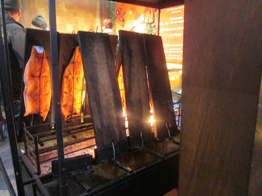 Salmon being smoked over a fire in the Weihnachtsmarkt outside the Kölner Dom