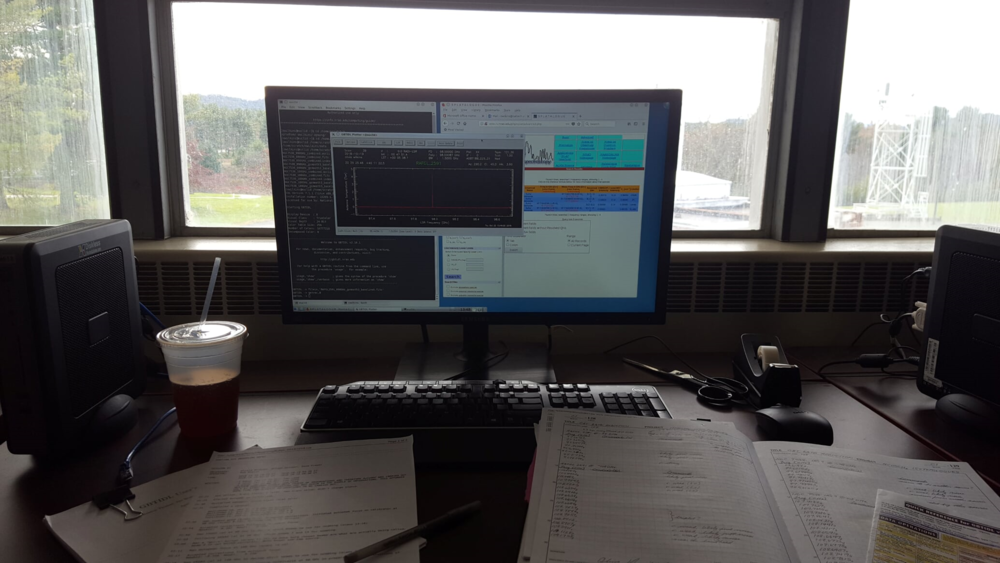 My workstation in the Jansky Lab library, featuring observation logs (left) and my research notebook (right). On the computer screen, there's some of my data (front), my command line terminal (back left), and an astronomical catalogue (back right) that helps me identify what I'm seeing in the data.