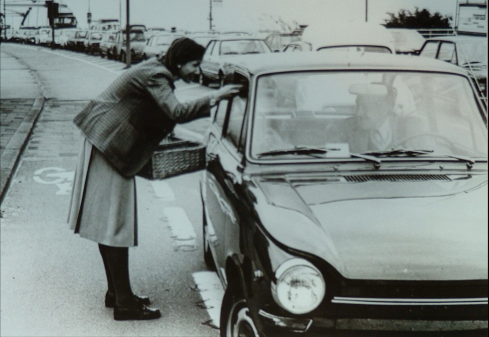 A city official distributes flyers and flowers to motorists, September 1977.  Image Courtesy of Groningen ImageBank.