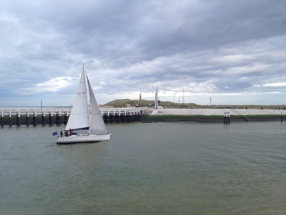 A sailboat sailing into Nieuwpoort