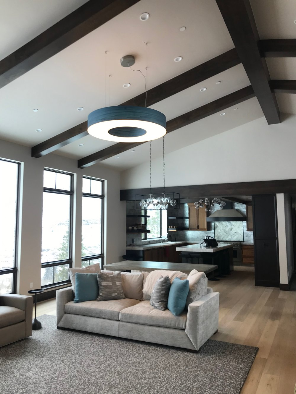 For the main living space, I chose a striking wood veneer LZF pendant in a hue that mimics Colorado bluebird skies. Coziness was key for this home—the homeowners both have dynamic, fast-paced jobs and wanted a space to disconnect from work and reconnect with their family. I chose Bernhardt sofas and covered them in textured, highly durable fabrics to provide a soft landing while incorporating the clean lines the homeowners love.