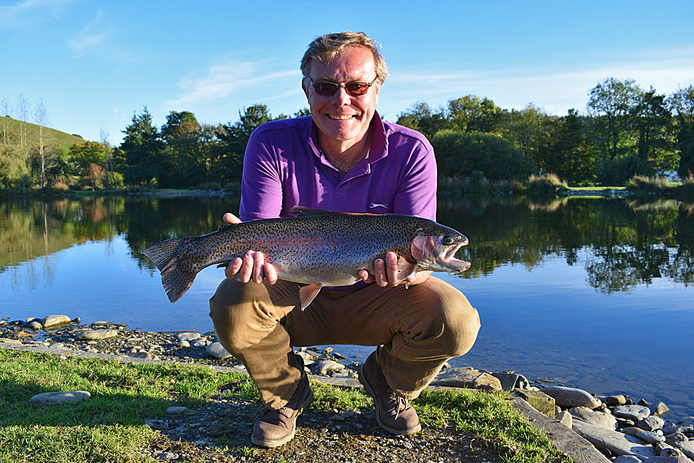 Just his third time fly fishing!  John Hall from Bridgwater looks very happy with this stunning 7lb Rainbow caught on a Buzzer during glorious sunshine.