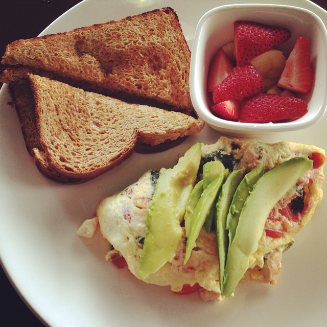 A hearty, balanced breakfast of fruit, gluten-free whole grain toast, a veggie egg white omelet and sliced avocado!