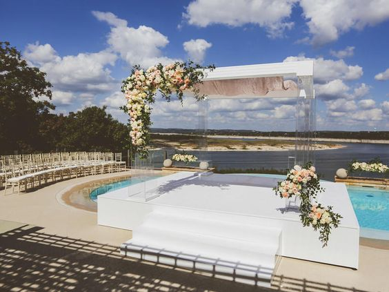 Lucite Chuppah dressed with flowers via The Knot