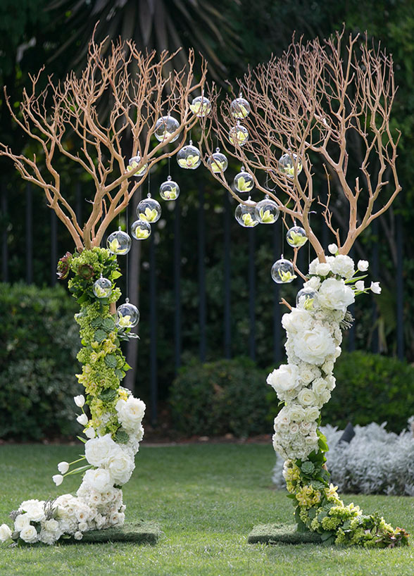 Archway built from manzanita trees dressed with flowers and glass bubbles for an outdoor wedding.
