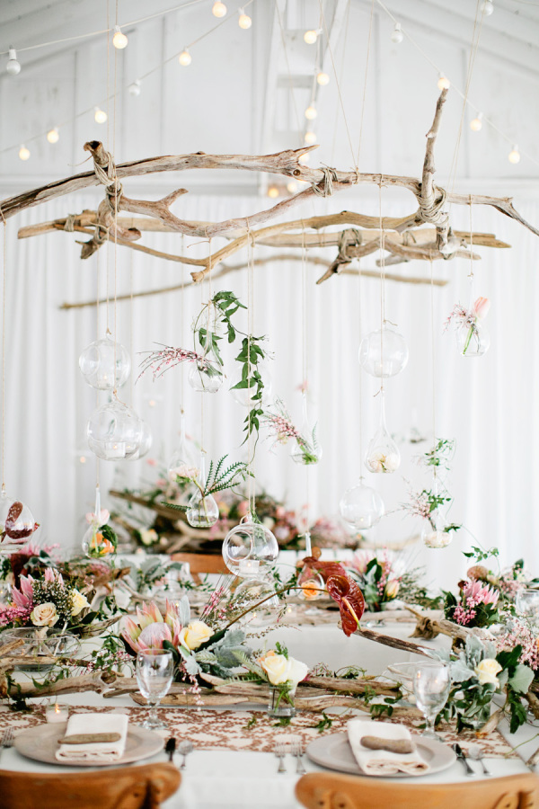 Driftwood pieces dazzle on the tables AND in the air space overhead in this lovely wedding set up.