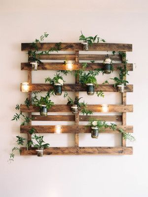 Hanging wall display constructed with reclaimed lumber and dressed with candles, flowers, and greenery.
