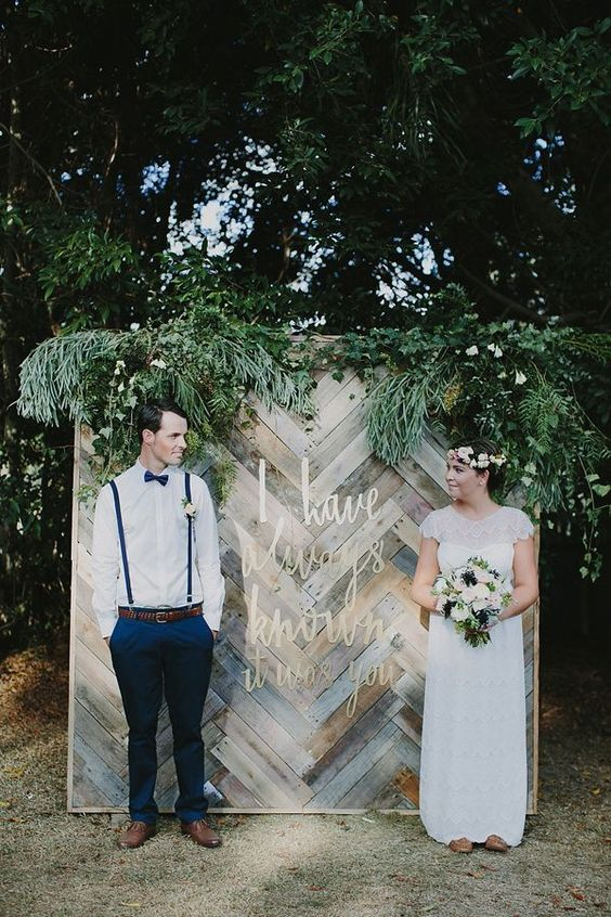 Beautiful display wall for a wedding featuring a chevron pattern made with reclaimed wood serves as a wonderful photo backdrop.
