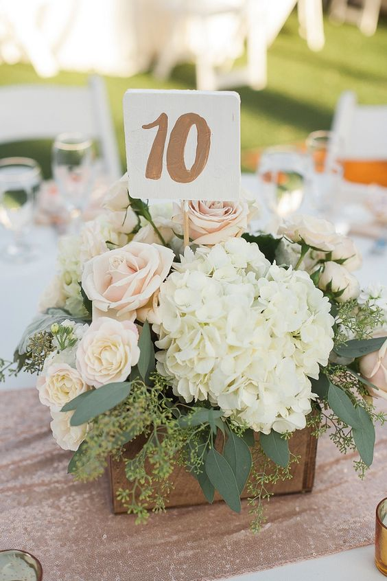 A floral centerpiece housed in a wooden containers performs double duty by also serving as a table number holder.