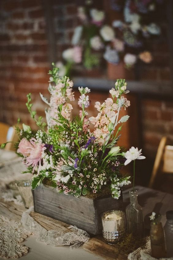 Wildflowers in a wooden container are a charming touch to a wedding as seen in this centerpiece.